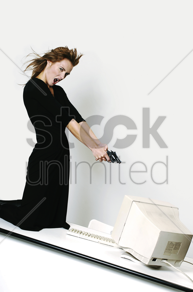 businesswoman pointing her pistol at a computer monitor stock photo