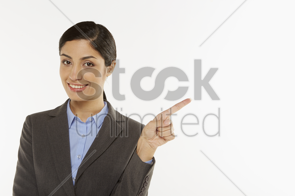 businesswoman pointing to the left, smiling stock photo