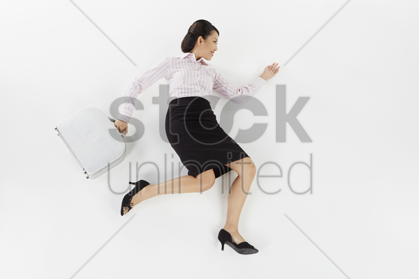 businesswoman posing on the floor with briefcase stock photo