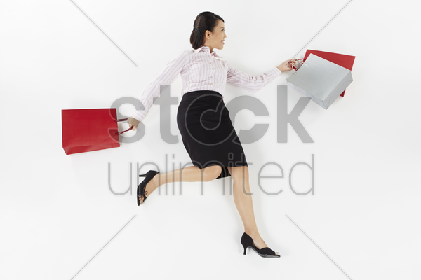 businesswoman posing on the floor with shopping bags stock photo
