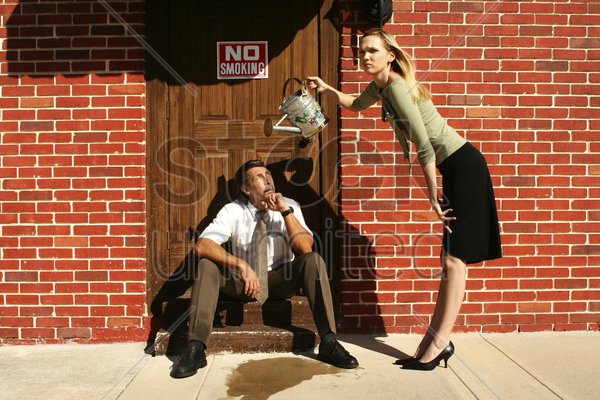 businesswoman pouring water at businessman's cigarette stock photo