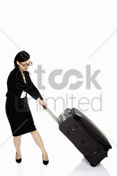 businesswoman pulling a heavy luggage bag stock photo