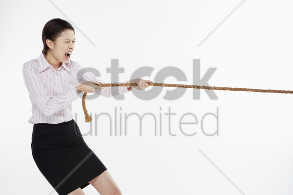 businesswoman pulling a tightrope stock photo