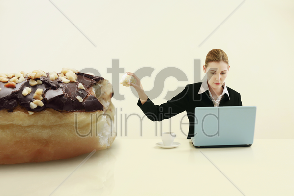 businesswoman pulling out a chunk of doughnut while using laptop stock photo
