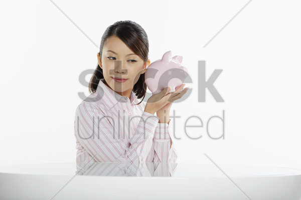 businesswoman putting ears against a piggy bank stock photo