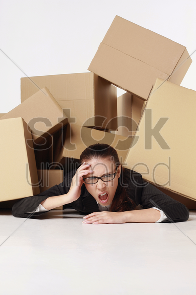businesswoman putting her hand on head while being buried under a pile of boxes stock photo