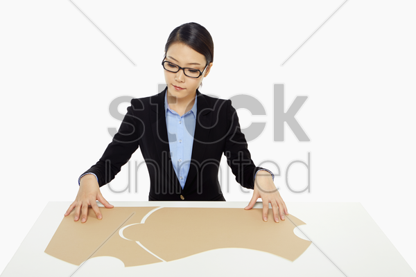 businesswoman putting together the puzzle pieces stock photo