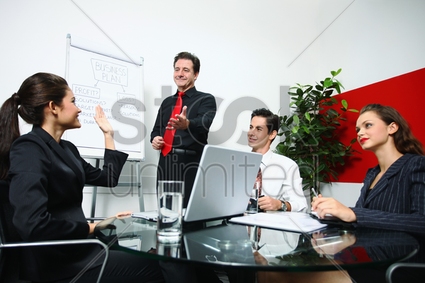 businesswoman raising her hand during business meeting stock photo