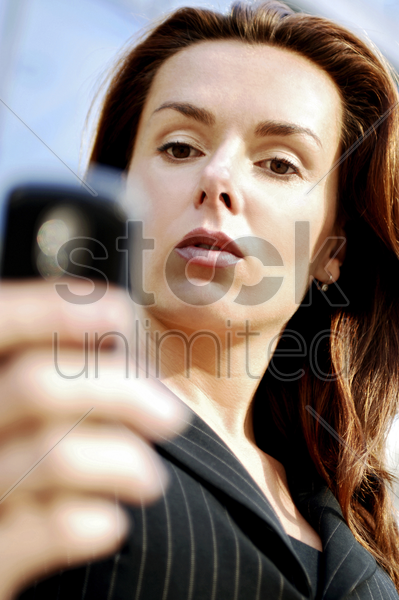 businesswoman reading messages on her mobile phone stock photo