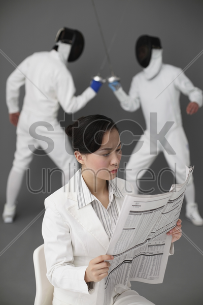 businesswoman reading newspaper with two men fencing in the background stock photo