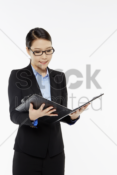 businesswoman reading notes from a folder stock photo
