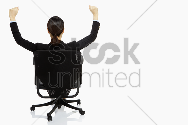 businesswoman resting on a chair, cheering stock photo