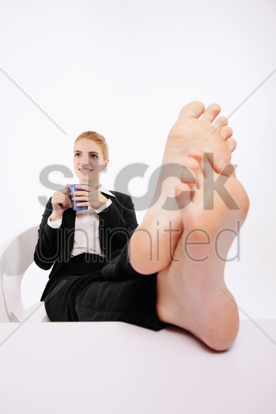 businesswoman resting with her legs up on a table while drinking coffee stock photo