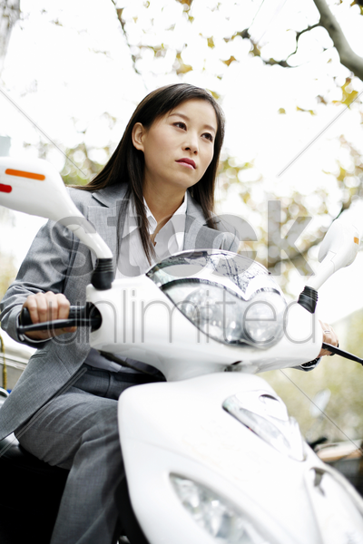 businesswoman riding on a scooter stock photo