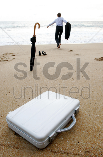businesswoman running to the sea leaving her things behind stock photo