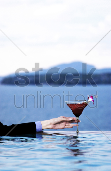 businesswoman's hand holding a glass of cocktail stock photo