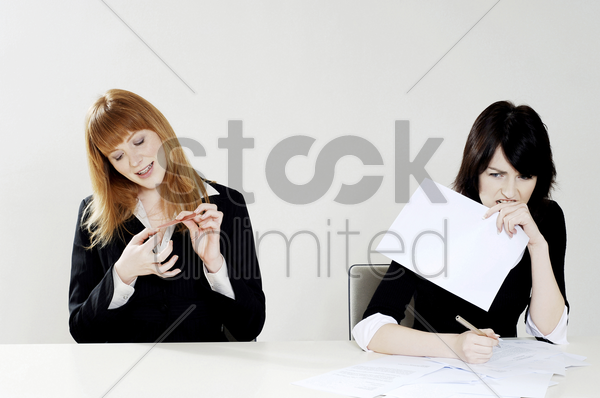 businesswoman shaping her fingernail while her colleague is busy doing her work stock photo
