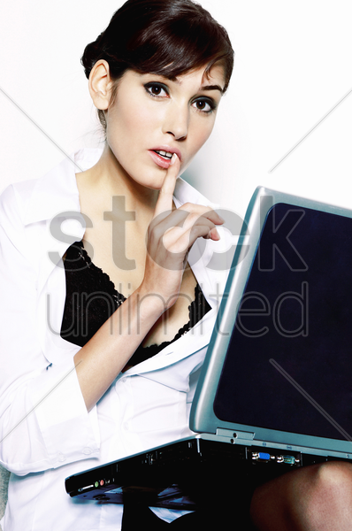 businesswoman showing a hushing sign stock photo
