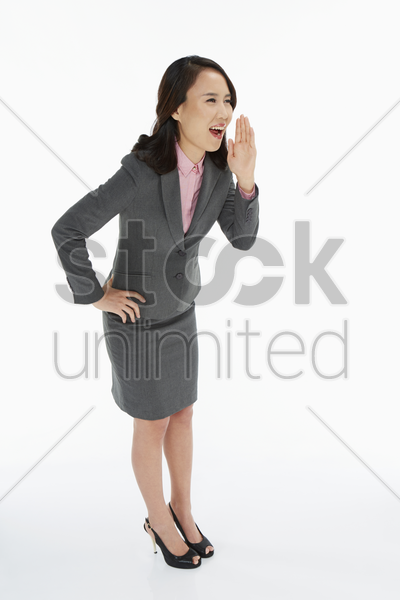 businesswoman showing a whispering gesture stock photo
