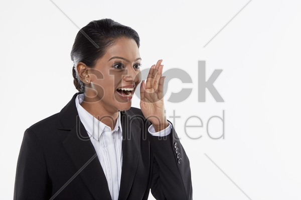 businesswoman showing a whispering hand gesture stock photo