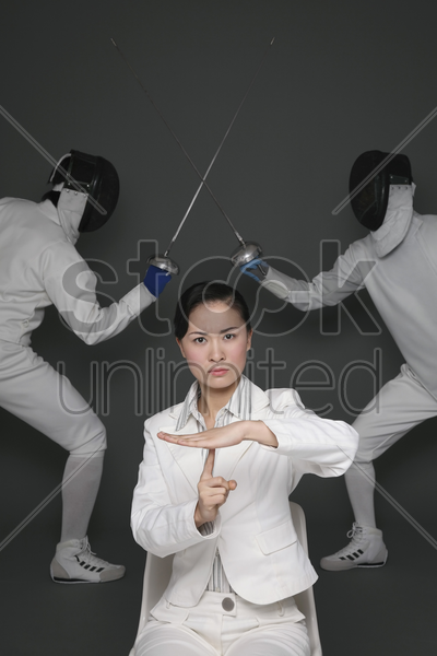 businesswoman showing time out with men dueling in the background stock photo