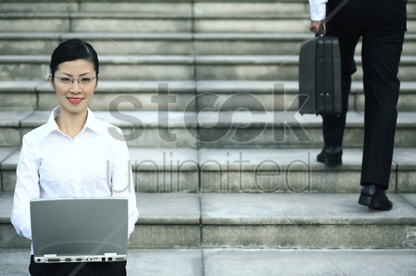 businesswoman sitting at the staircase using laptop stock photo