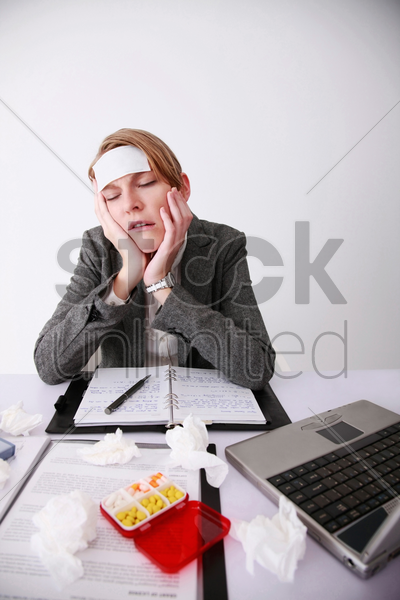 businesswoman sitting at the table, having cold and flu stock photo