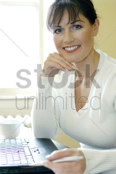 businesswoman sitting in front of a laptop stock photo