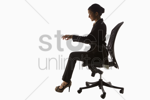 businesswoman sitting on a chair, pretending to type stock photo