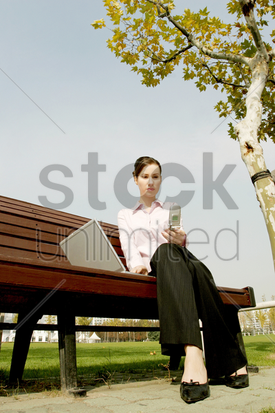 businesswoman sitting on the bench text messaging and using laptop stock photo