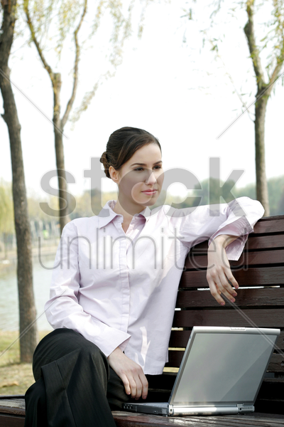 businesswoman sitting on the bench thinking while using laptop stock photo