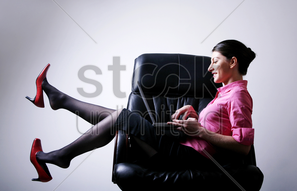businesswoman sitting on the chair playing with laptop stock photo