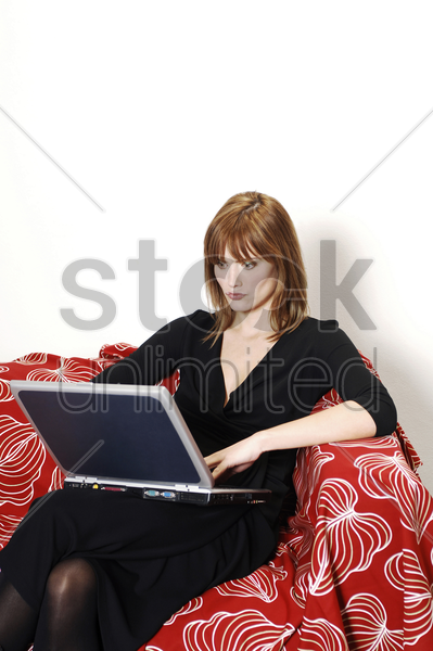 businesswoman sitting on the couch using laptop stock photo