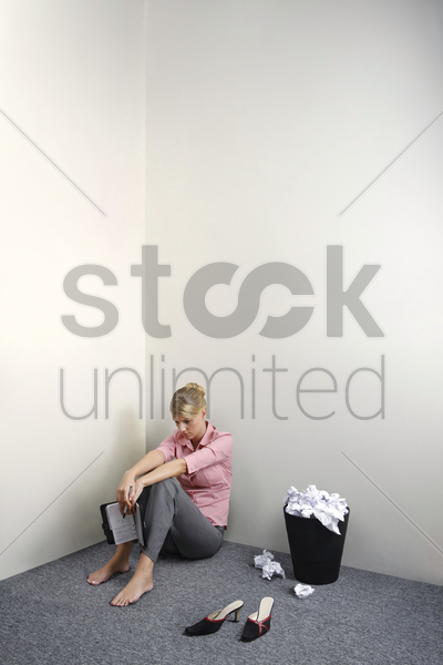 businesswoman sitting on the floor holding organizer stock photo