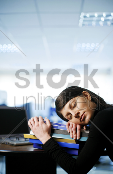 businesswoman sleeping with her head on a stack of books stock photo