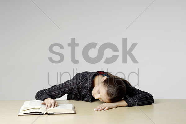 businesswoman sleeping with her head on the table stock photo