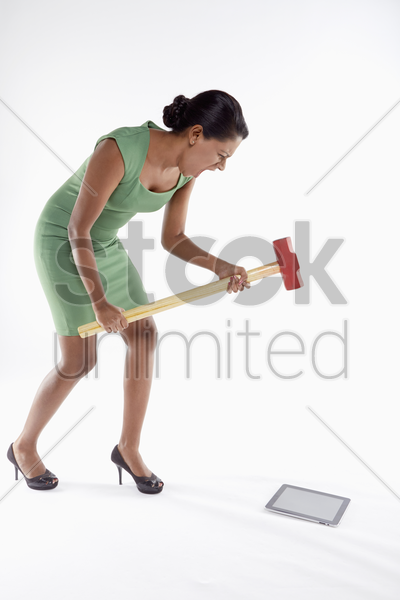 businesswoman smashing digital tablet with a hammer stock photo