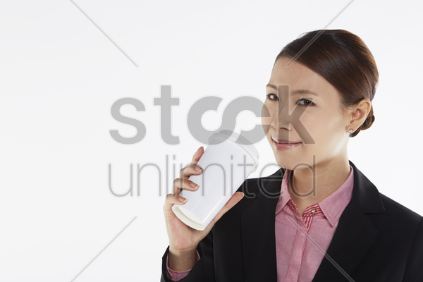 businesswoman smiling and holding a disposable cup stock photo