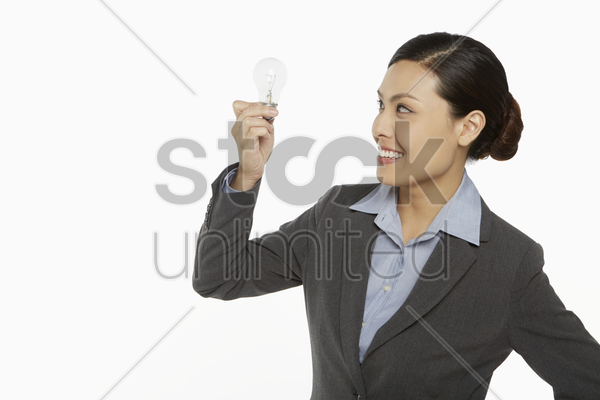 businesswoman smiling and holding up a light bulb stock photo