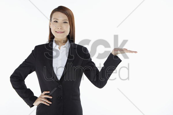 businesswoman smiling and showing hand gesture stock photo