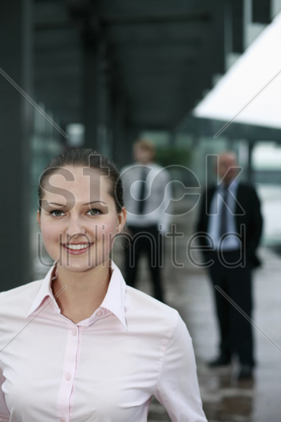 businesswoman smiling, businessmen in the background stock photo