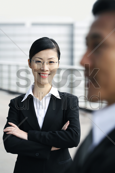 businesswoman smiling while folding her arms stock photo