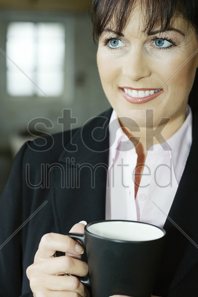 businesswoman smiling while holding a cup of coffee stock photo