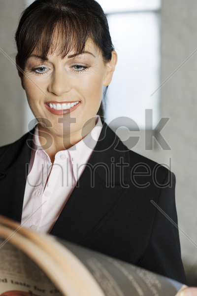 businesswoman smiling while reading newspaper stock photo
