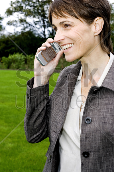 businesswoman smiling while talking on the mobile phone stock photo