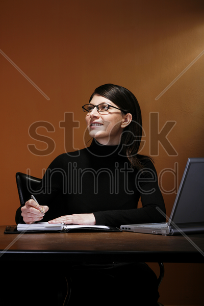 businesswoman smiling while writing her organizer stock photo