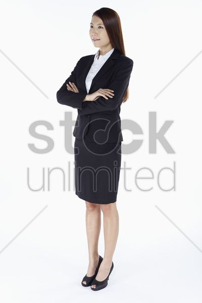 businesswoman smiling with arms crossed stock photo