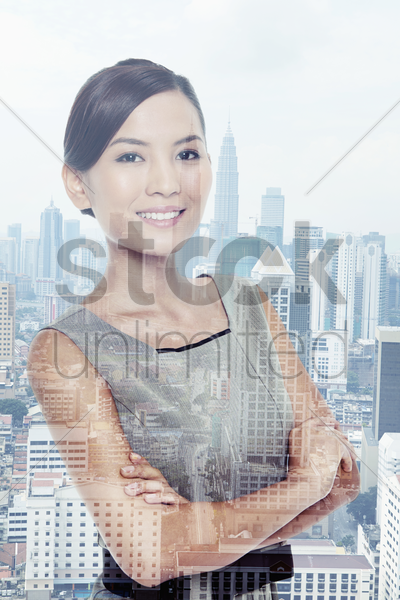 businesswoman standing against a cityscape background stock photo