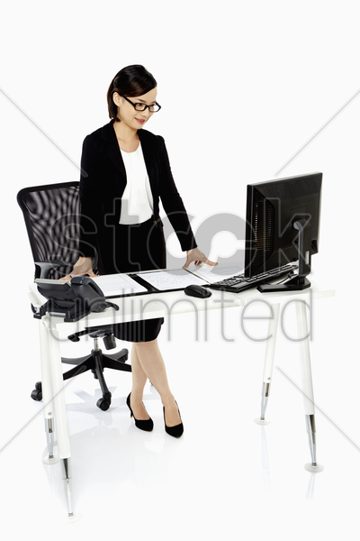businesswoman standing and looking at her notes stock photo