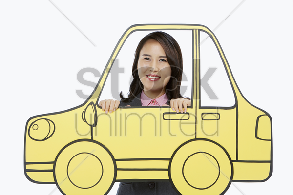 businesswoman standing behind a cardboard car stock photo